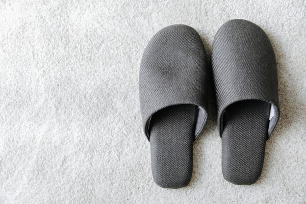 High Angle View Of Gray Flip-Flops On Carpet