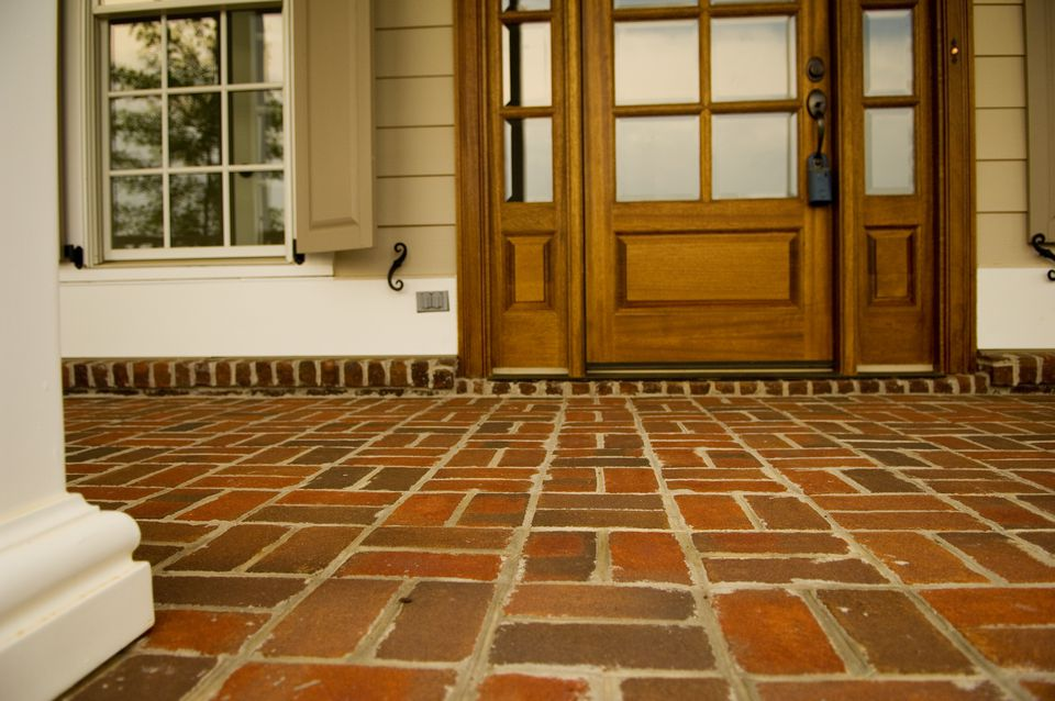Low view of a front porch made of brick.