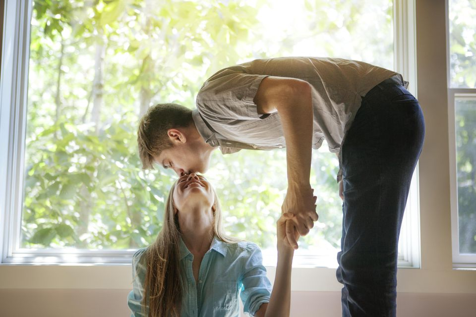 Man Leaning Over Girlfriend and Kissing Forehead