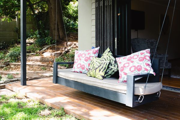 Homemade dark wood porch swing with a tan cushion and multicolored pillows