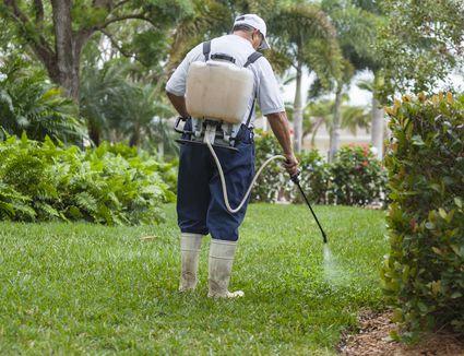 Pest control technician with portable spray rig using spray nozzle and hose