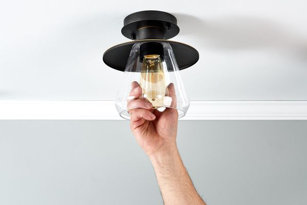 person unscrewing a light bulb in a fixture