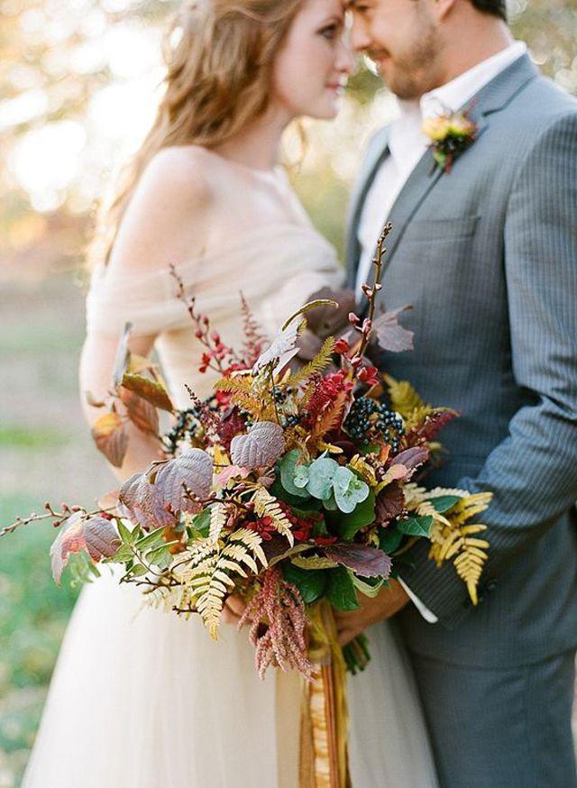 Joven novia y el novio con un ramo de boda rústico