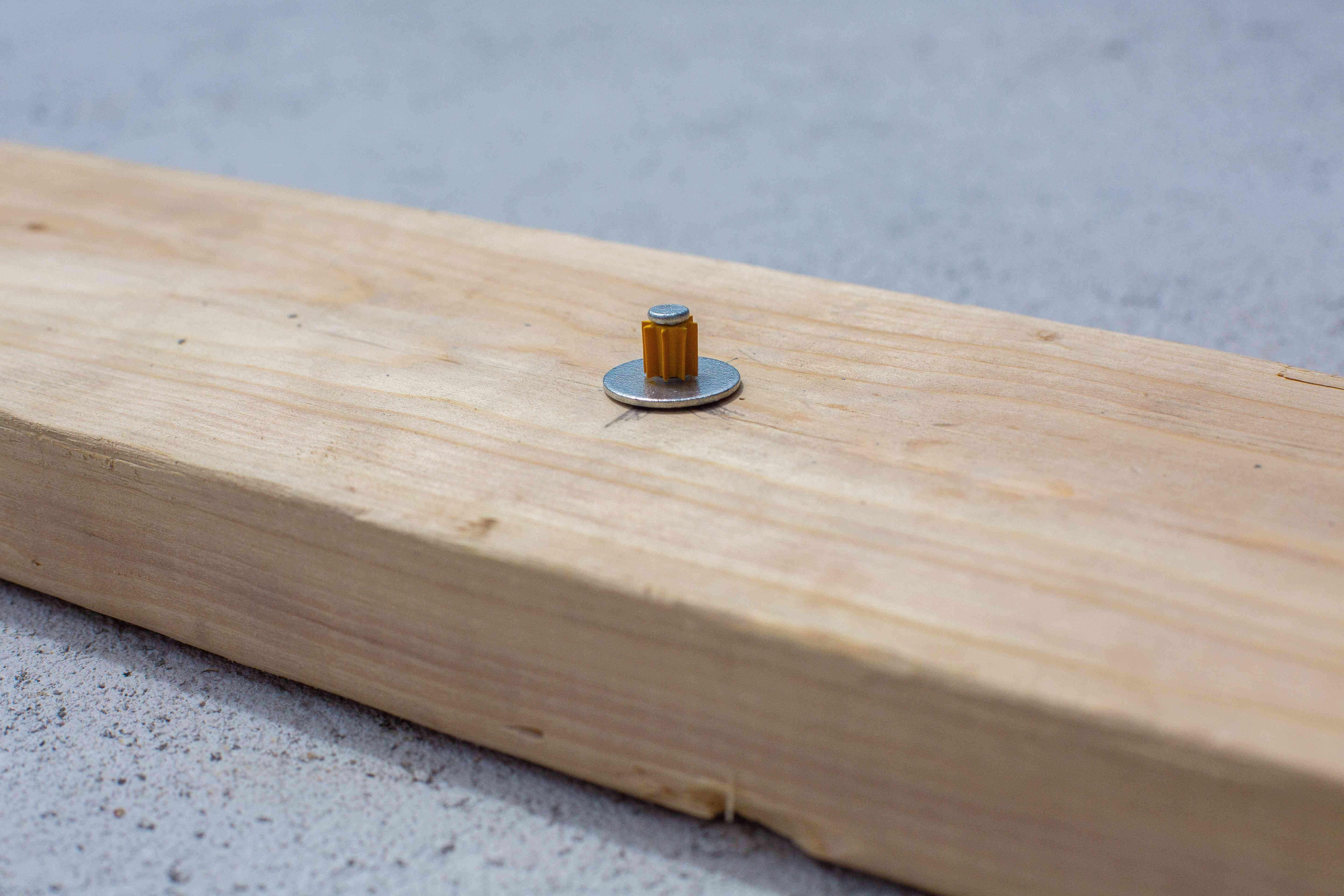 Nail above wooden board surface with spacer closeup