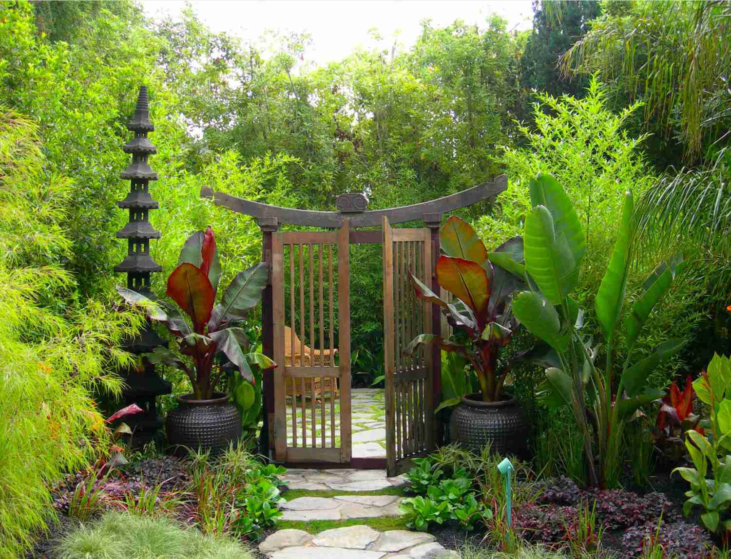 Vertical garden near stone walkway with doors leading to more space.