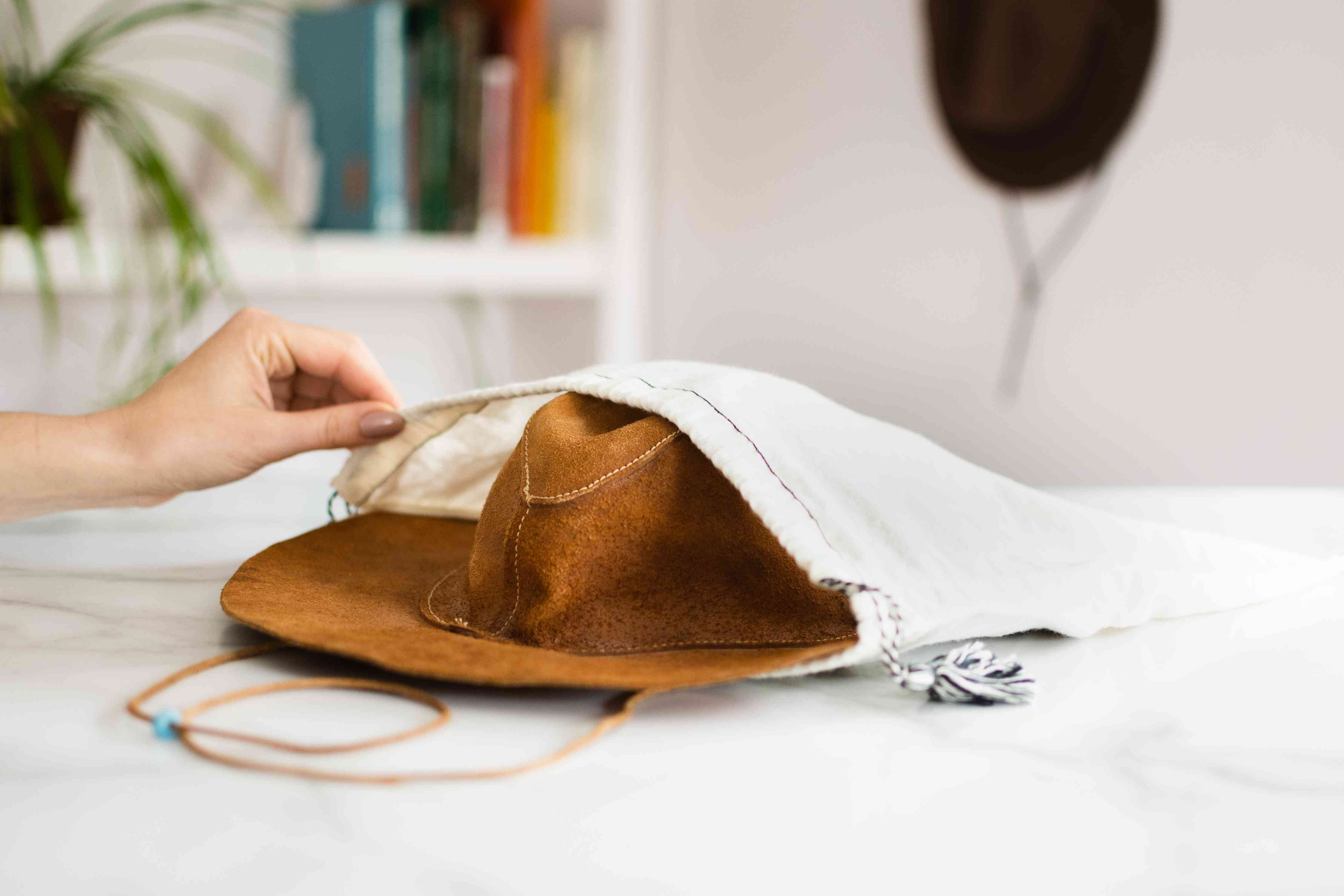 Light brown leather hat stored in a white cloth garment bag