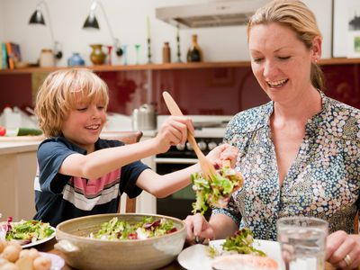 Son helping to serve salad for mother at the family dinner table