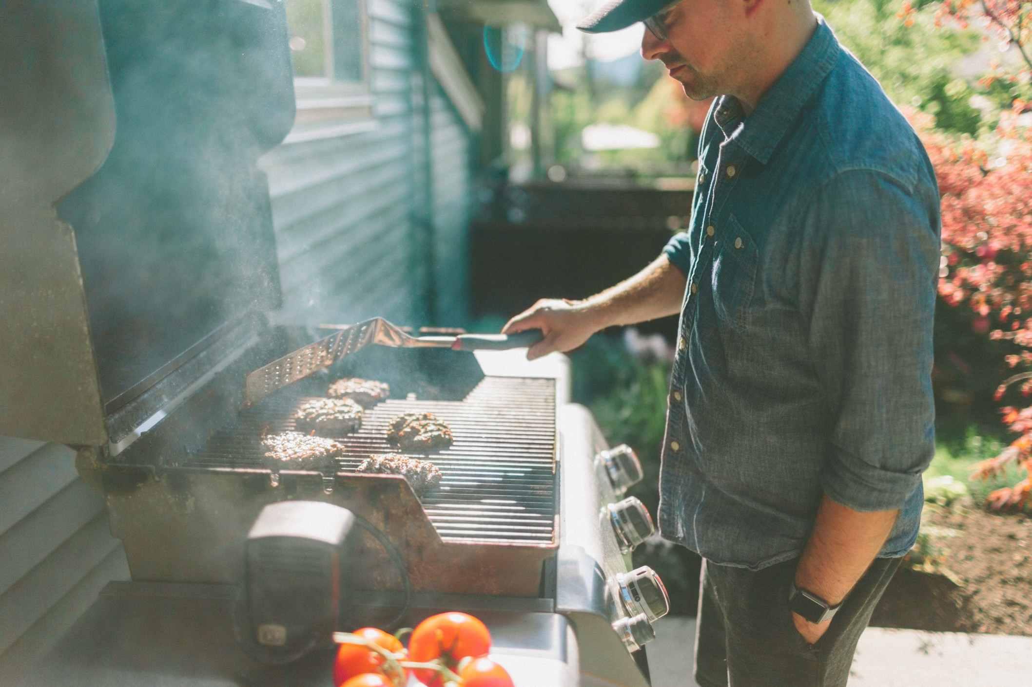 Hombre asando hamburguesas