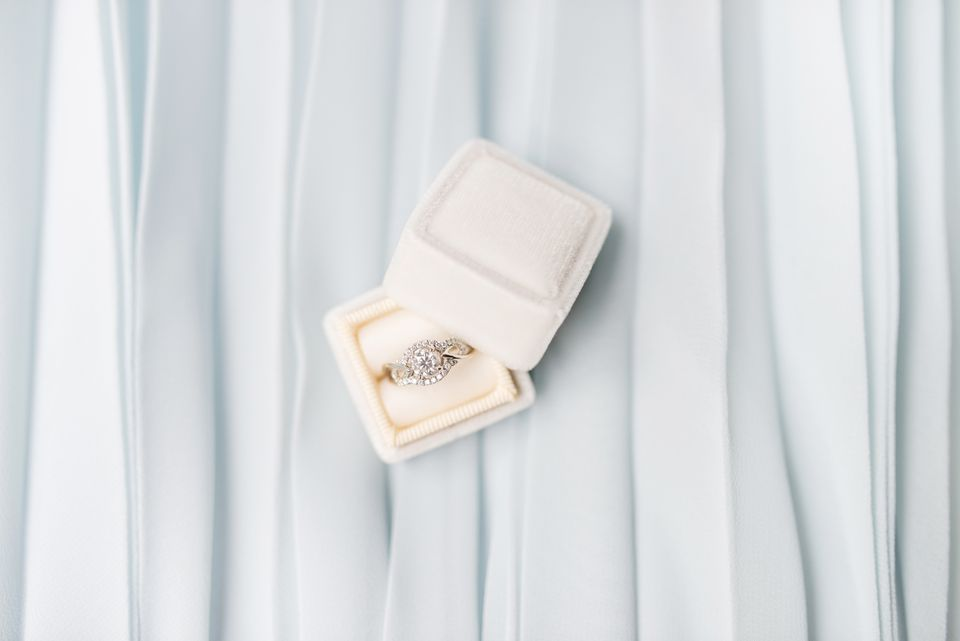 An engagement ring in box on light blue background