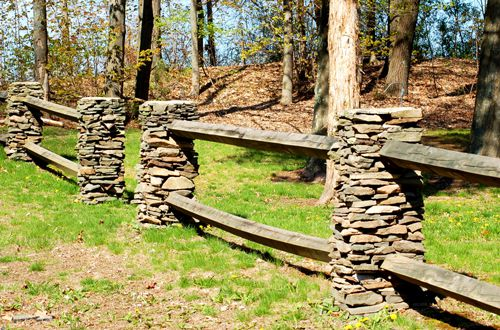 Photo of a split-rail fence with stone pillars.