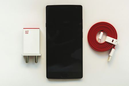 High Angle View Of Smart Phone With Charger On White Table