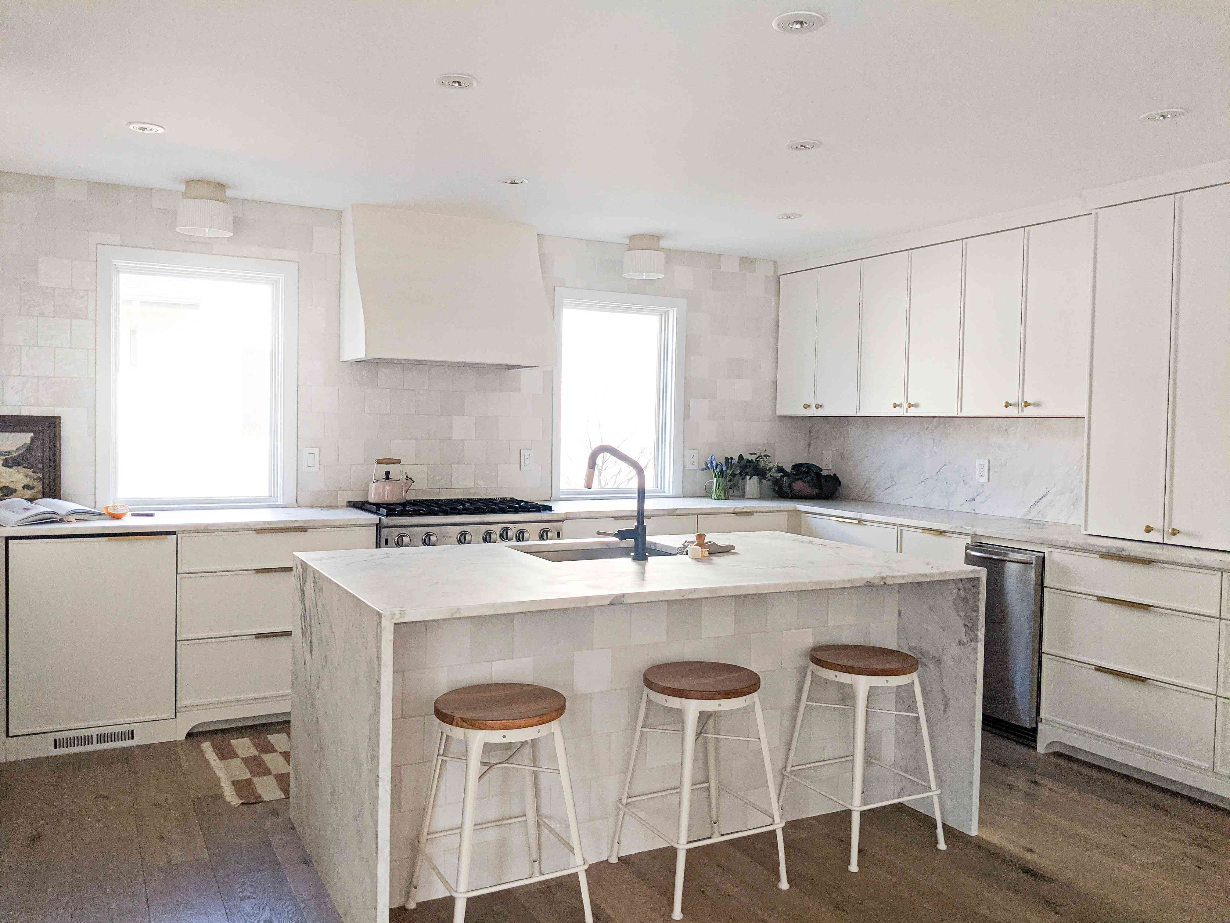 The white kitchen in the Shaker Heights home of Molly & Fritz features a marble waterfall island, black hardware, and windows on either side of the range