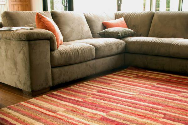 Striped area rug over hardwood in living room.