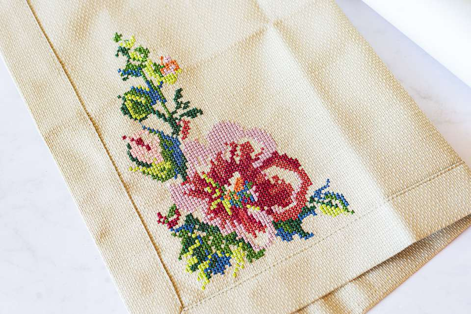Tan fabric with floral cross-stitching