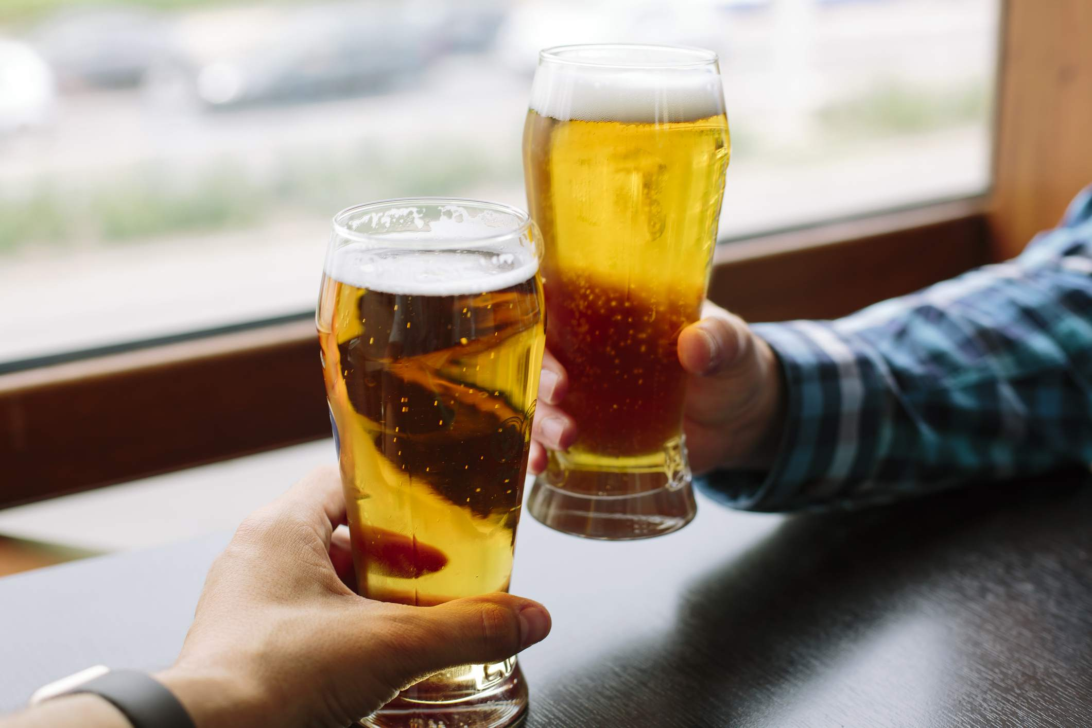 Two friends toasting with pints of beer.