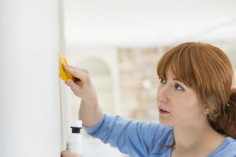 woman patching drywall with putty knife