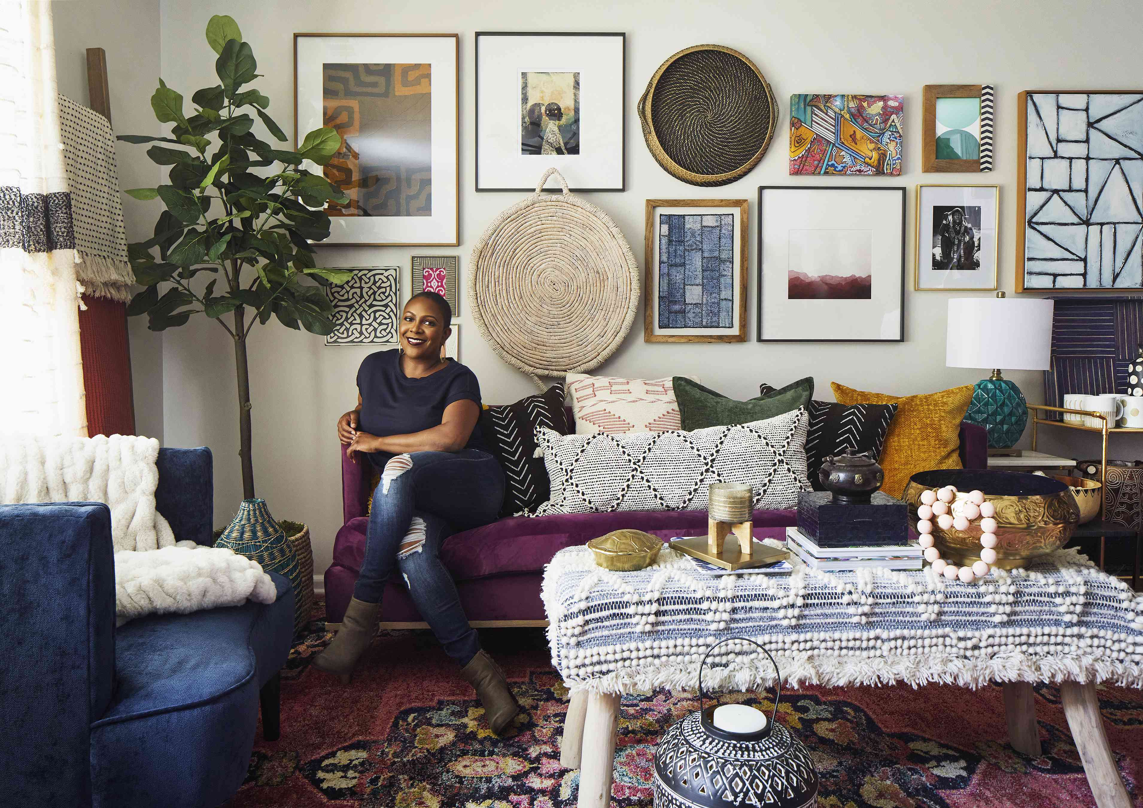 Beth Diana Smith poses on a purple couch in a room with boho chic decor