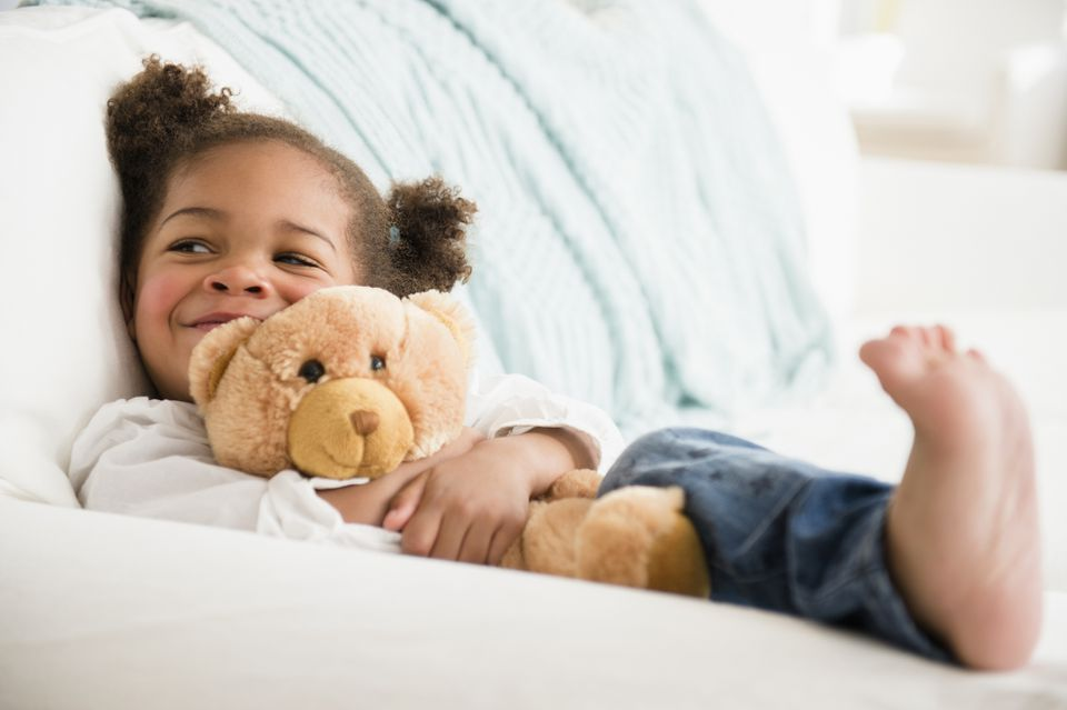 Black girl hugging teddy bear and smiling