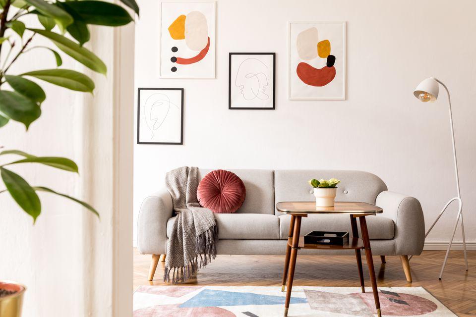 Una sala blanca con acentos neutros y coloridos cuadros abstractos colgando detrás del sofá.
