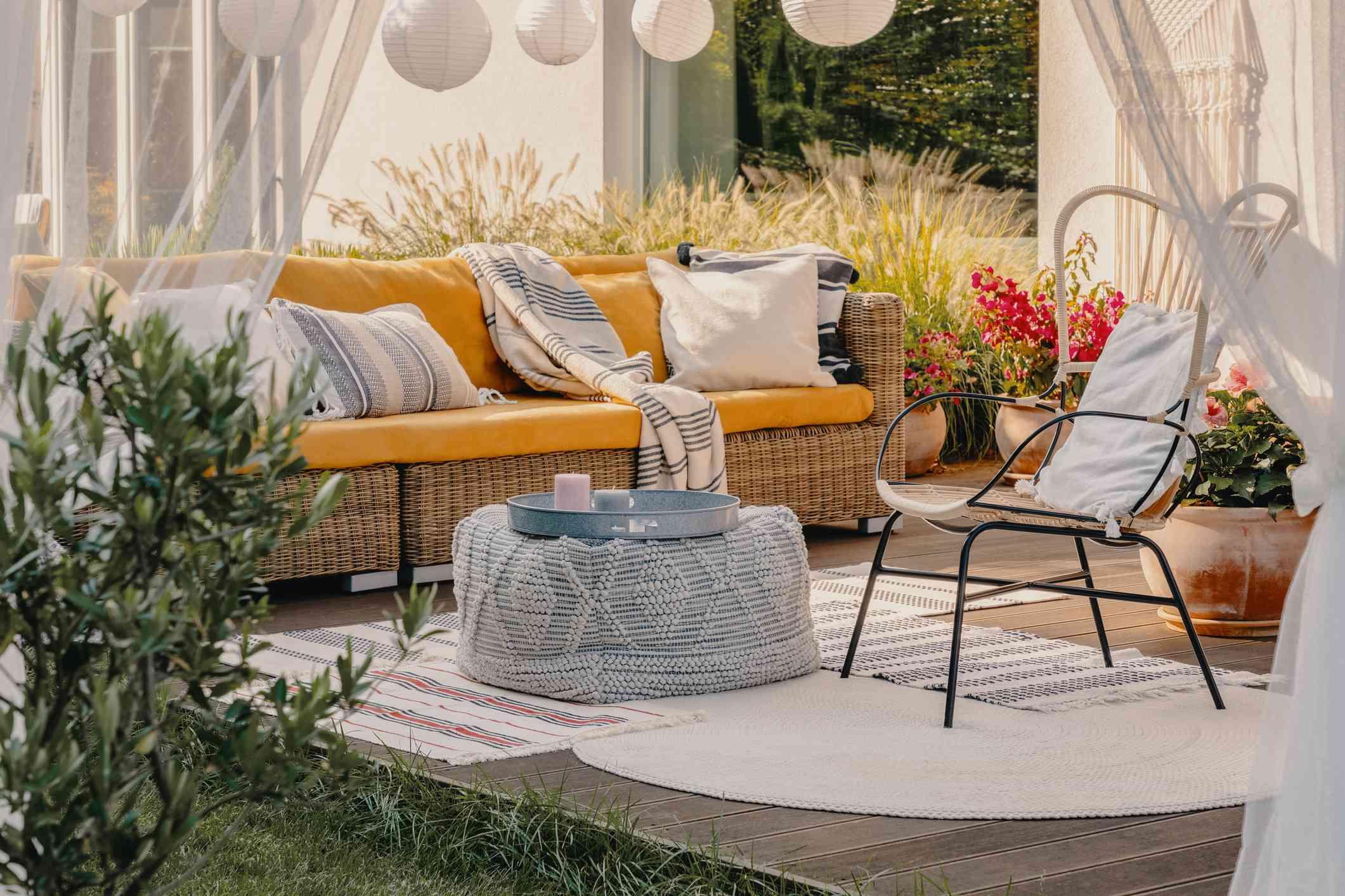 Foto real de un sillón, puf como mesa y sofá de mimbre en una terraza