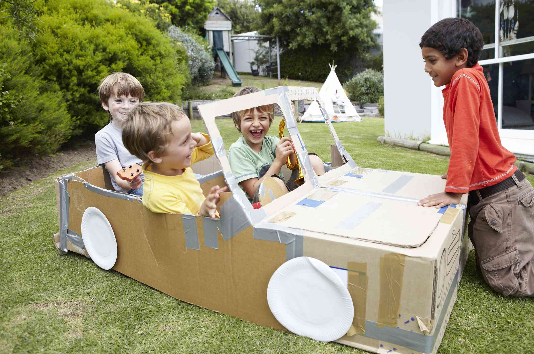 Group of boys playing in cardboard car