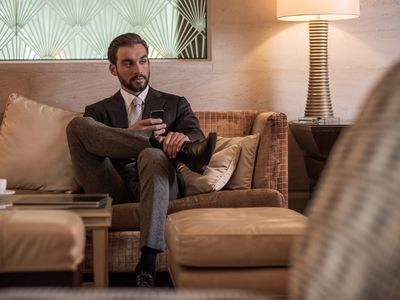 Snobby businessman sitting in couch.