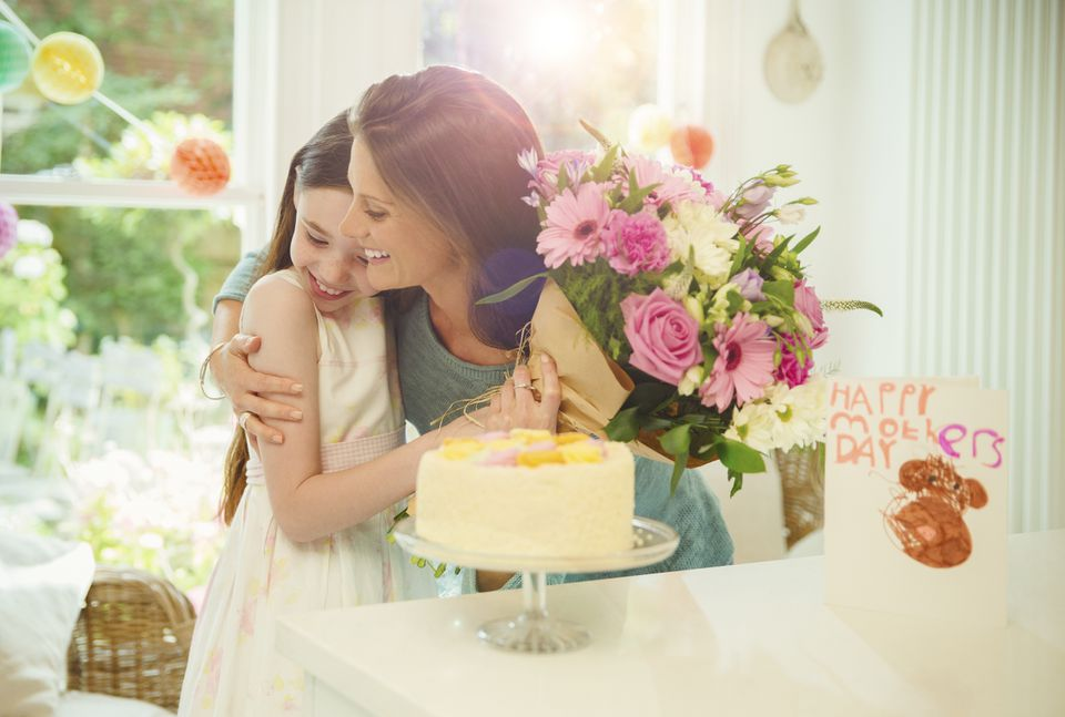 Affectionate daughter giving flower bouquet to mother on MotherÕs Day