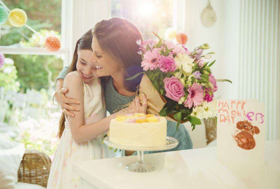Hija cariñosa que da un ramo de flores a la madre en el Día de la Madre