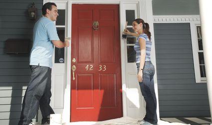 Couple painting doorframe on front door of house