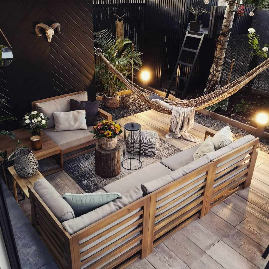An outdoor room with black privacy walls, wood furniture and a hammock