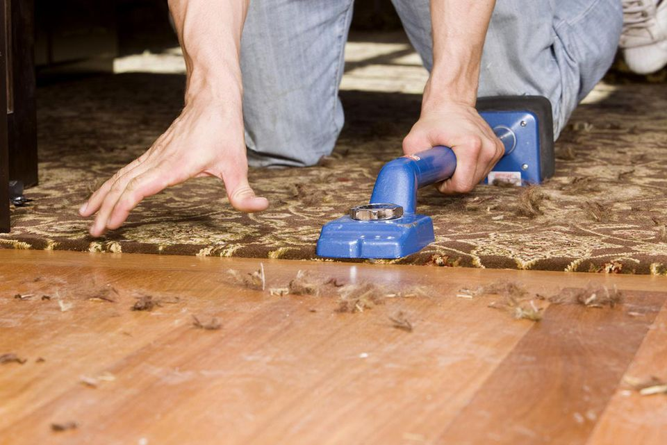 Installer using knee kicker to stretch home office carpet