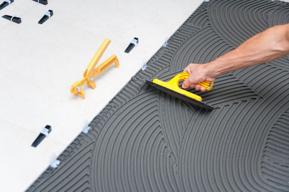 Installing tile using a rubber grout float system