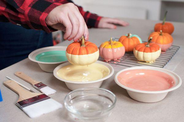 Hand dipping mini pumpkin