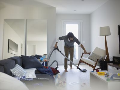 Man vacuuming under chair