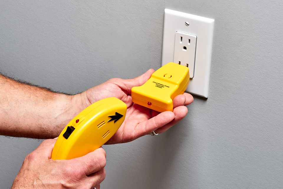 Yellow circuit breaker finder inserted into wall outlet