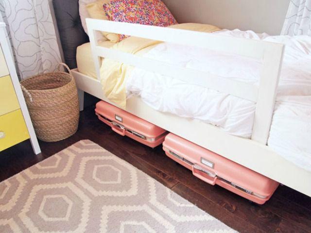 Maletas rosadas guardadas debajo de una cama