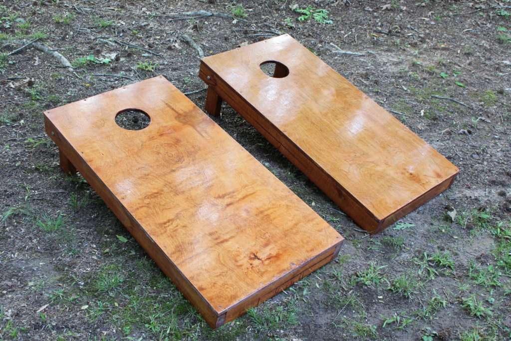 Two cornhole boards in a yard