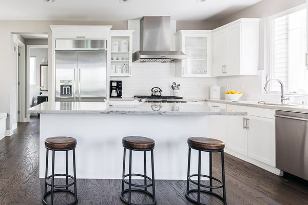 White kitchen island with marble countertop and brown bar stools in front