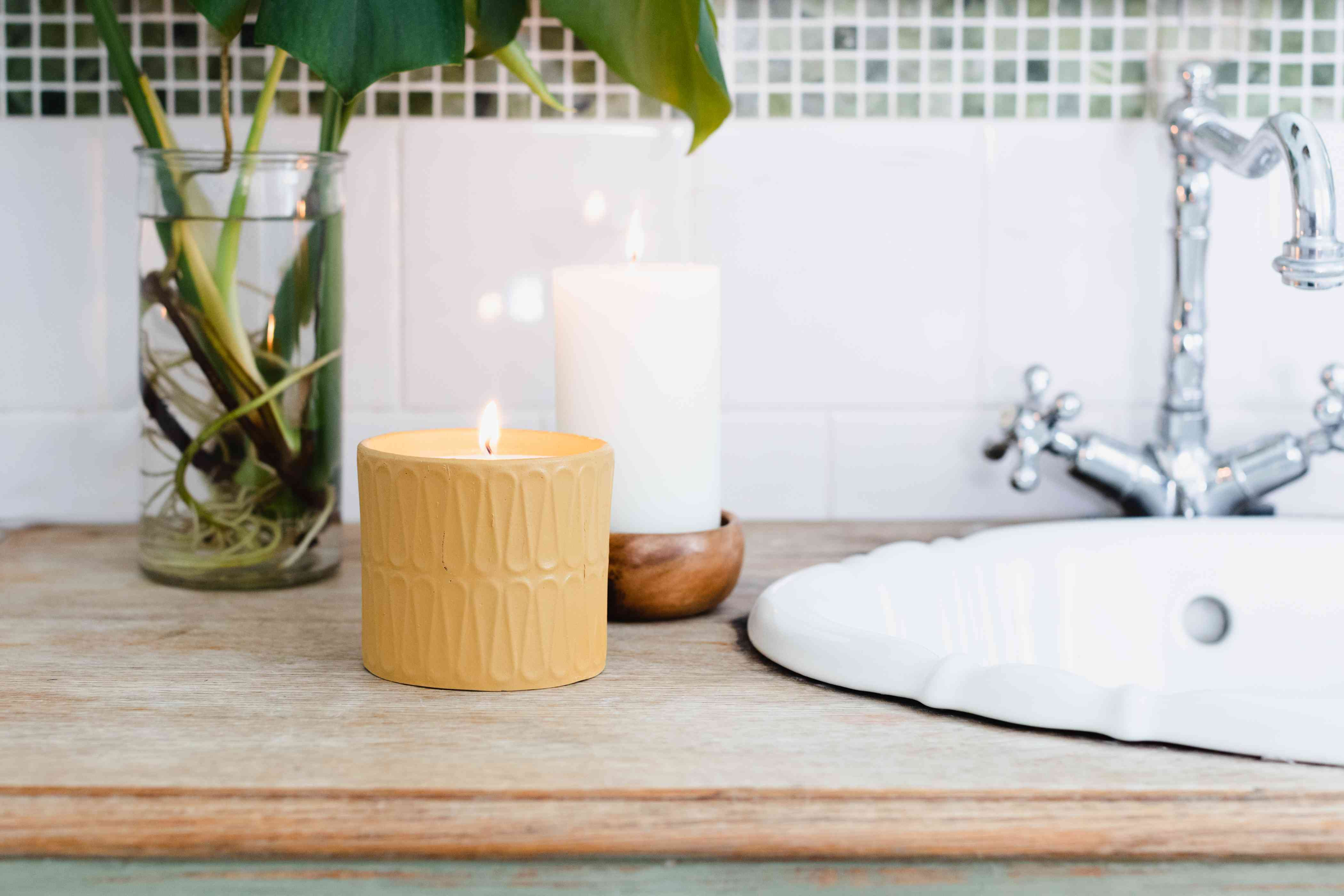 Two lighted candles on bathroom vanity surface reducing bathroom odors