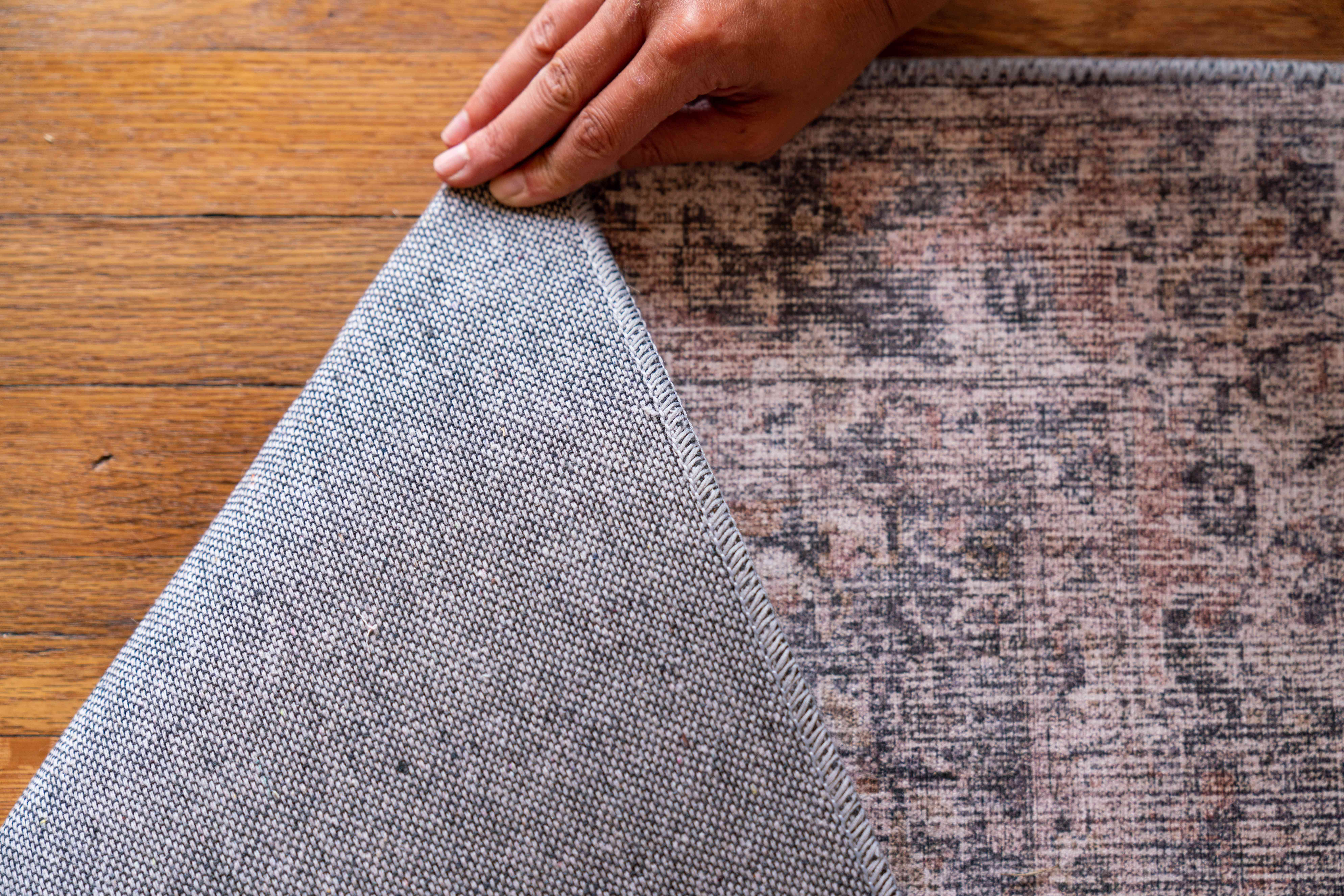 Light pink, tan and gray hand-tufted rug flipped over to to show mechanized and hand-made pattern