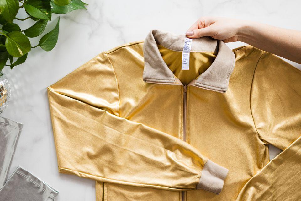 Yellow metallic jacket folded on left arm being held up