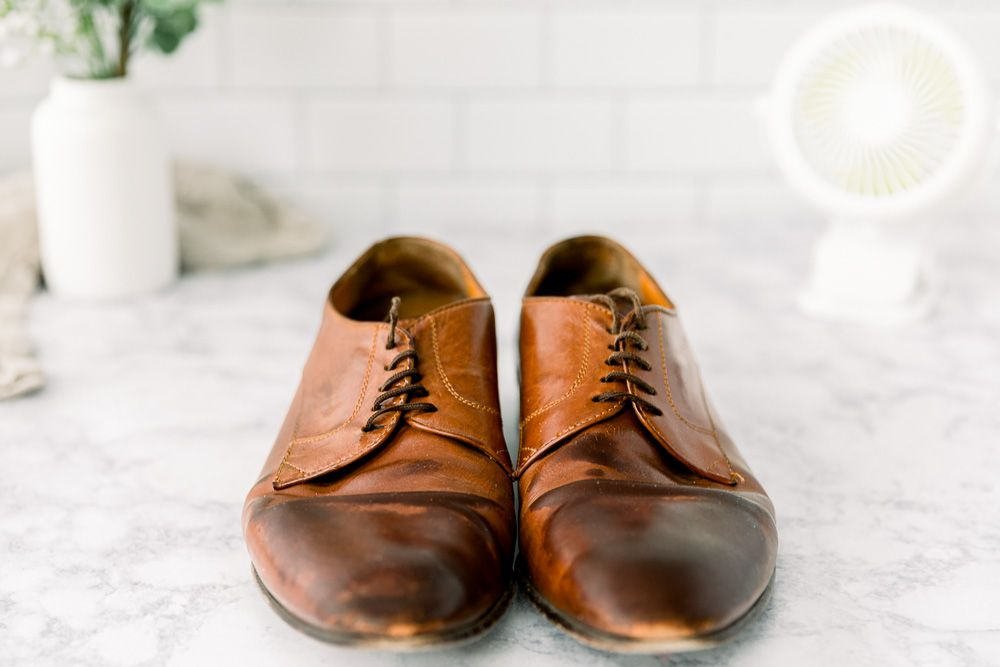 Brown leather shoes sitting on a counter with a fan
