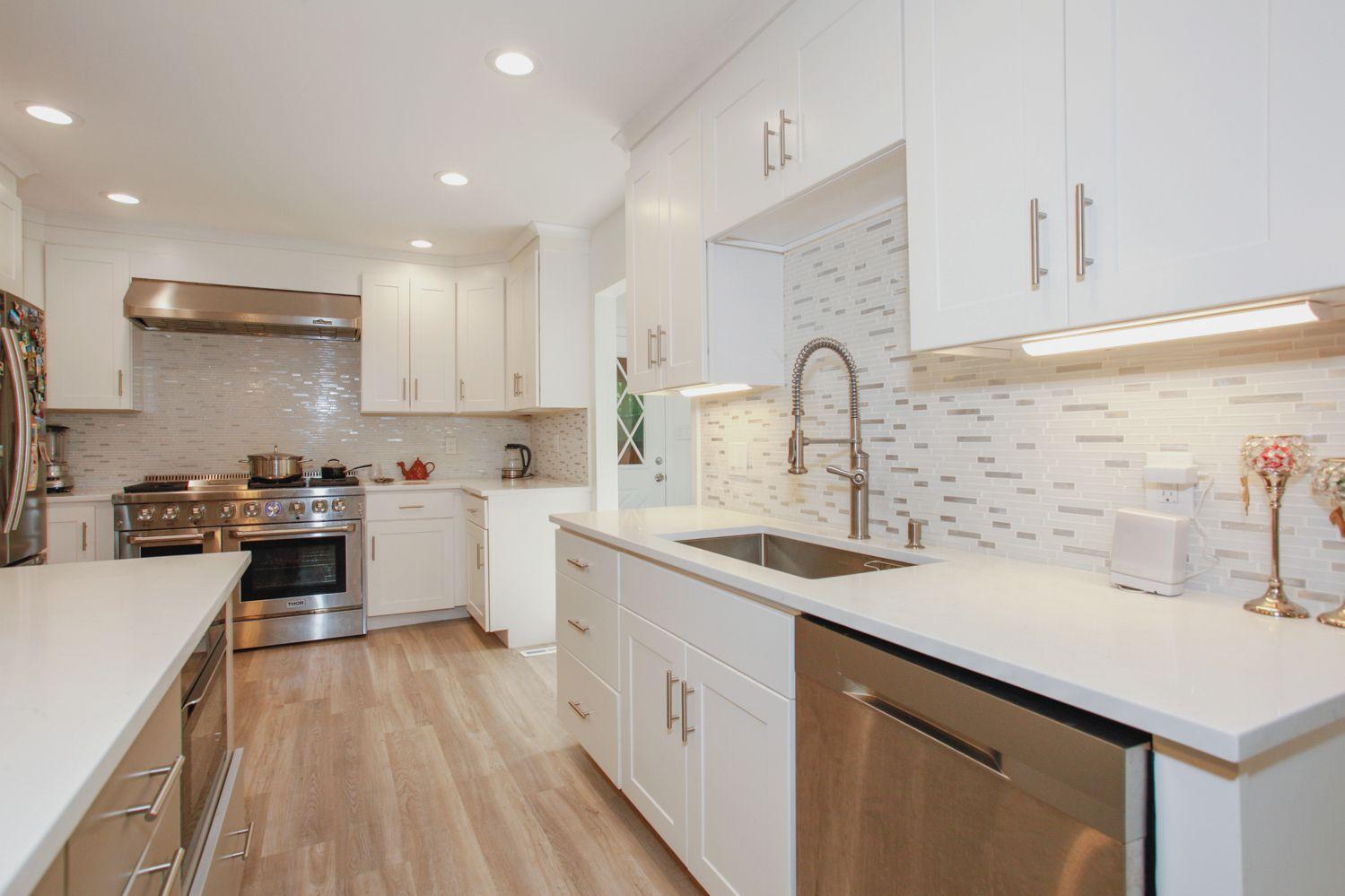 cocina blanca con electrodomésticos de acero inoxidable