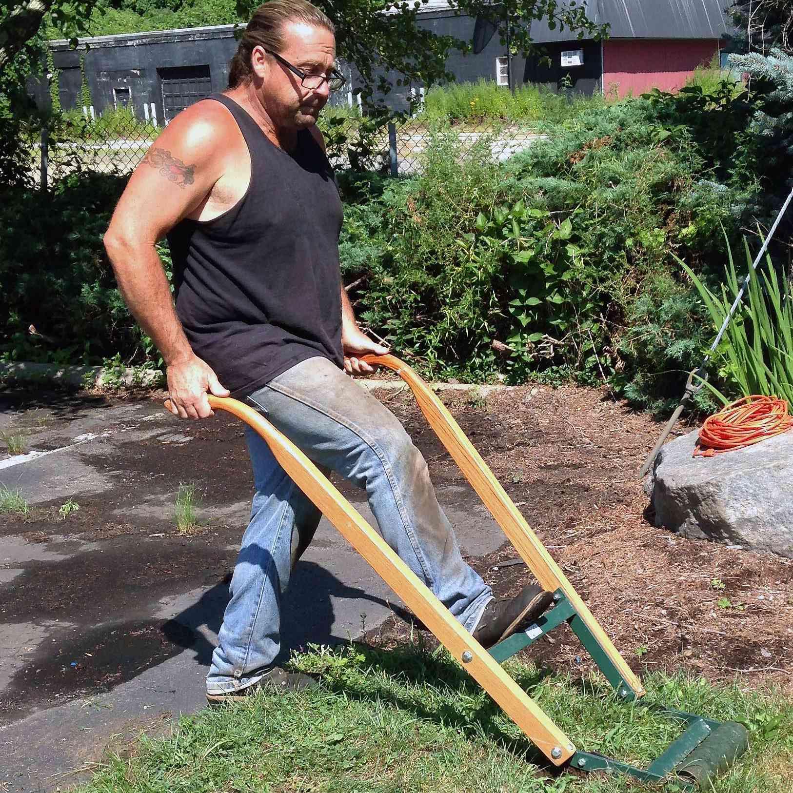 Man pushing manual sod cutter