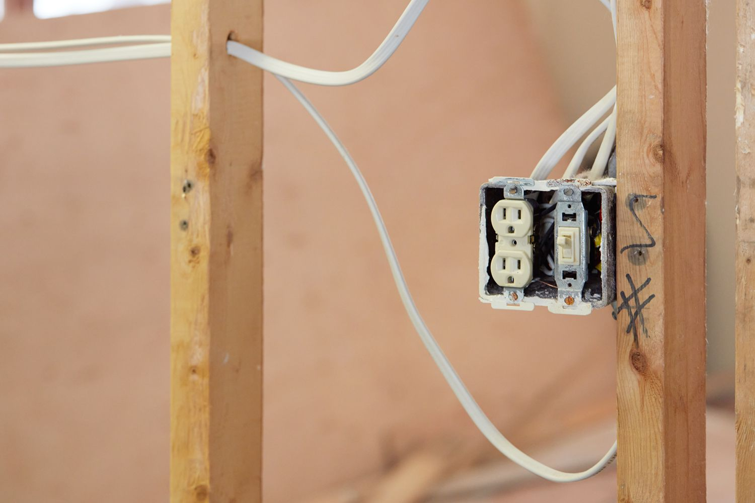 Exposed electrical outlet in between drywall wooden beams and wires