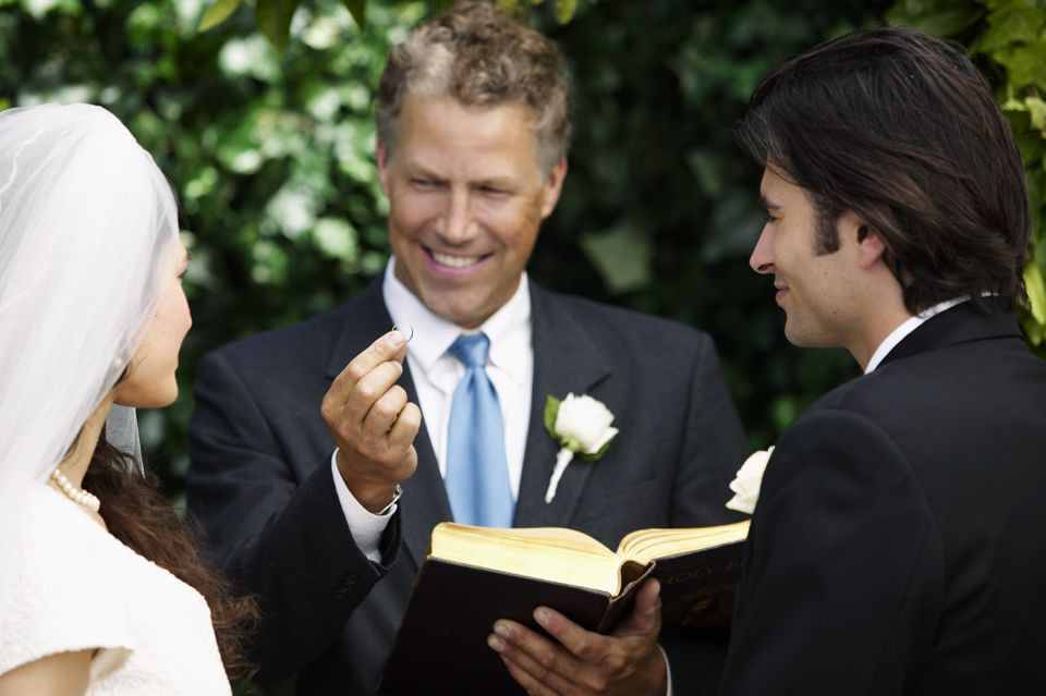 Wedding officiant guides couple through vows.