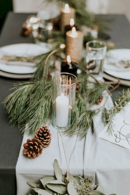 Centro de mesa de boda de invierno de hoja perenne, piña y vela