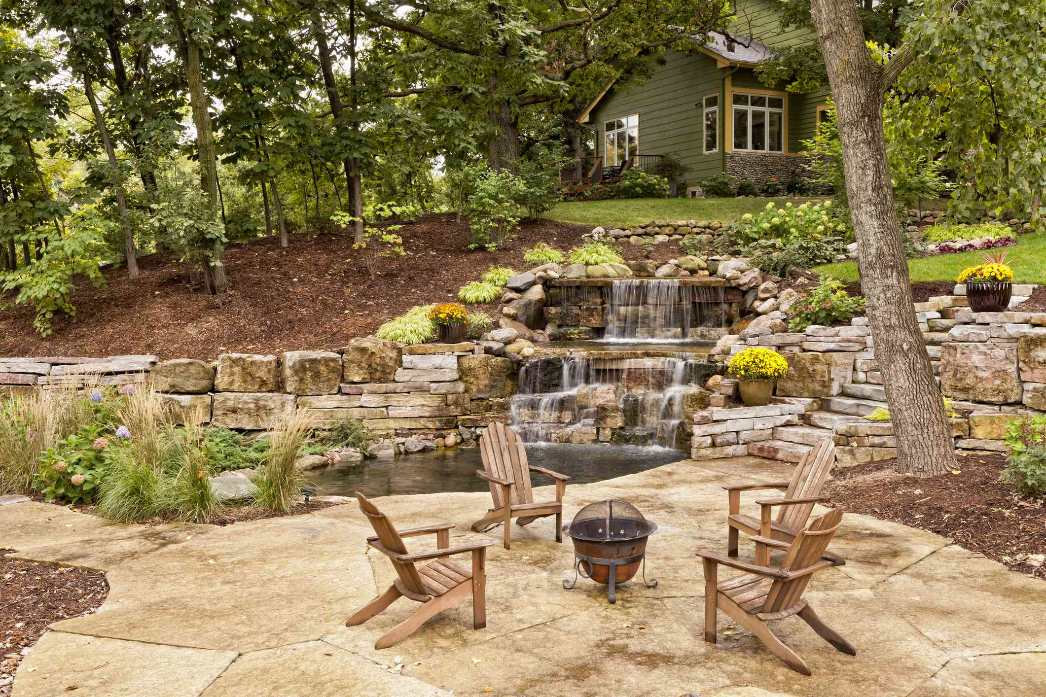 Four chairs around a fire pit next to a koi pond with waterfalls.