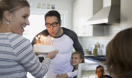 Father blowing out birthday cake candles in kitchen