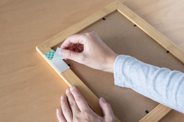 Back of wooden picture frame with double-sided tape cover being removed